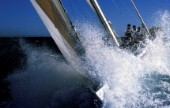 Bow of racing yacht crashes through a wave in rough seas