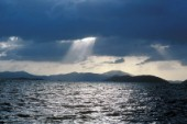 Suns rays through clouds over silhouetted islands