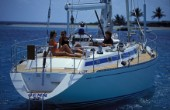 Girls relaxing on the deck of a Swan 55 at anchor by Sandy Island in the Caribbean