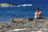 Fit man sitting on ragged rocks near the sea in pensive moment