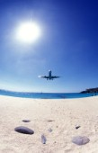 Plane arriving at St Martin airport next to beach
