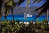 Windsurfer sails passed anchored yacht off the island of Eustatia, Caribbean