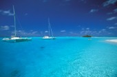 Two cruising catamarans anchored in clear, shallow water - Seychelles