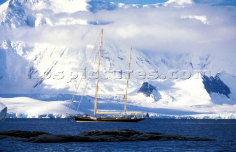 Maxi cruising yacht anchored in a bay beneath snow covered mountains