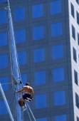 Crew member climbing mast of maxi yacht in front of office block
