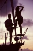Silhouette of couple on bow of anchored cruising yacht