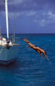 Two girls dive off the side of an anchored Swan yacht