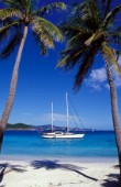 Yacht at anchor off tropical beach  Cruising yacht anchored off beach in shallow water, Caribbean.
