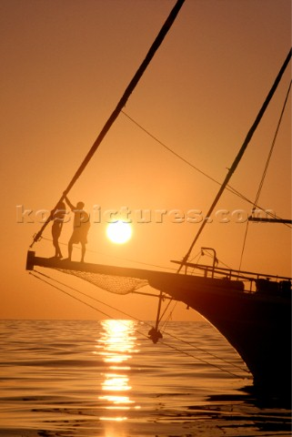 Romantic couple on bowsprit of classic yacht