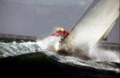 Crew on rail of yacht in rough seas during the Fastnet race