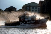 Spray from a bow wave flies over a Port of London Authority Dive vessel