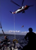Emergency helicopter coastguard rescue from a sailing cruising yacht