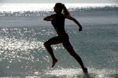 Silhouette of woman running through water along beach