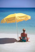 Woman sits alone on beach lookin out to sea under the shade of a yellow umbrella