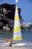 Model on beaced sailing dinghy with the sail up