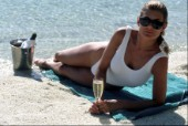 Woman lying on beach with glass of champagne