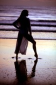 Woman in swimsuit strikes a pose on wet sand