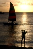 Woman standing on beach watching man in sailing dinghy at sunset