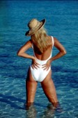 Model wearing straw hat and white swimsuit standing in shallow water with hands on hips