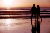 A couple take a romantic walk on a secluded beach at sunset