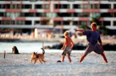 A father and son play with their dog on a sandy beach