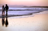 A couple take a romantic walk along a deserted beach at sunset