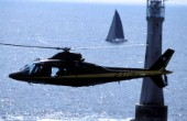 Helicopter flys passed Eddystone lighthouse whilst filming a racing yacht during the Fastnet Race