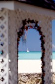 Boat through arch on sandy beach - Antigua