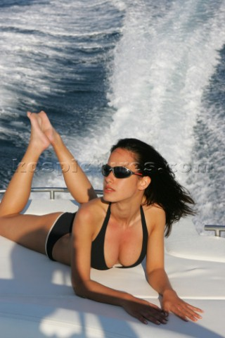 A glamorous model onboard a luxurious powerboat in the Mediterranean