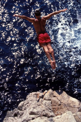 Musto man high diving into the sea from a cliff in Majorca