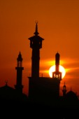 Silhouette of mosque towers at sunset, Dubai - United Arab Emirates.