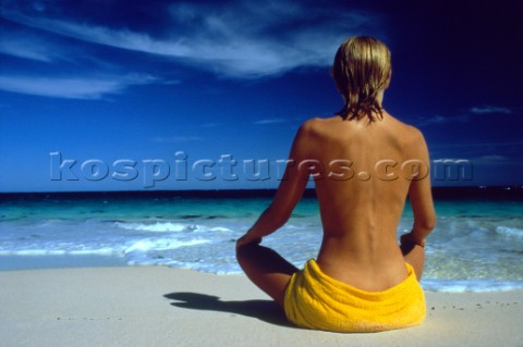 Woman sitting on beach looking out to sea
