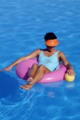 Woman floating on rubber ring in swimming pool