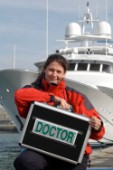 Female Doctor with medical kit in front of superyacht
