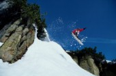 Snowboarder jumping off rocky outcrop.