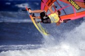 Close up of windsurfer jumping off wave