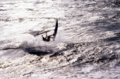 Silhouette of windsurfer jumping wave