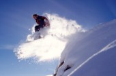 Snowboarder jumps off snowy ledge.