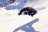 Snowboarder and his shadow mid air.