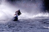 Jet Skier racing across flat water