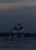 P&O cruise ship Aurora with navigation lights at night turning sharply to avoid collision with a small sailing yacht in restricted waters
