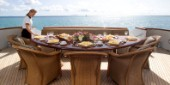 Stewardess sets dining table on aft deck of superyacht