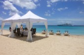 Jet skis lined up on sandy beach next to table set for lunch under white awning