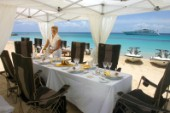 Table layed for lunch under awning on sandy beach with superyacht anchored in distance