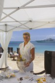Superyacht stewardess prepares lunch for guests on Caribbean beach