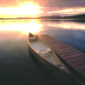 Canadian canoe moored to wooden jetty at sunset