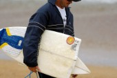 Competitor holds a broken surfboard at the Rip Curl Championship 2005