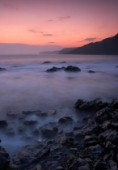 Motion effect of water lapping on shore under pink sky