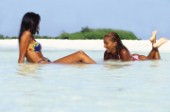 Two girls in bikinis lying in shallow water on sandy beach.