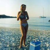 Girl in bikini standing on sandy beach with bottle of beer, Corscia